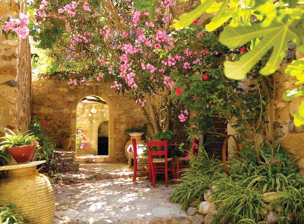 Czerwone krzesła, gliniane donice i jasne, kamienne mury – nawet bez palm można wykreować w ogrodzie śródziemnomorski klimat.